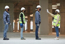 Side View Full Length Of Female Supervisor Measuring Temperature Of Workers With Contactless Thermometer At Construction Site, Corona Virus Safety Measures