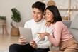 Leinwandbild Motiv Japanese Millennial Couple Using Digital Tablet Sitting Together At Home