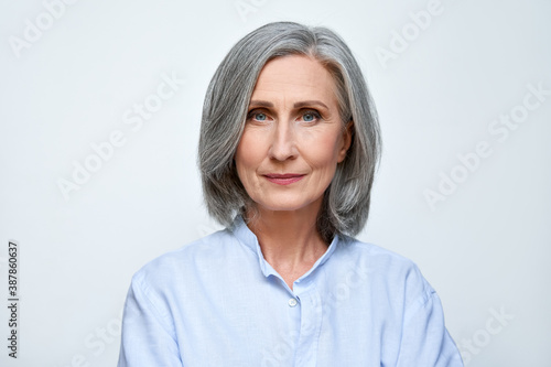 Obraz Confident beautiful mature business woman standing isolated on white background. Older senior businesswoman, 60s grey haired lady professional looking at camera, close up face headshot portrait. - fototapety do salonu