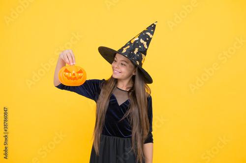 Fotografia, Obraz halloween child in witch hat hold pumpkin jack o lantern for witchcraft, happy h
