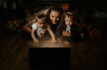 Halloween Holidays, Online Holiday Party In The Time Of COVID. Happy Family, Mother And Baby Celebrating Halloween Near Laptop, Online Meeting In New Normal, Pandemic Time.