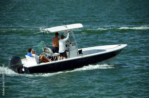 Three men and a woman enjoying a leisurely morning cruise on the Florida Intra-Coastal Waterway in an open sport fishing boat powered by a single outboard engine Fotobehang