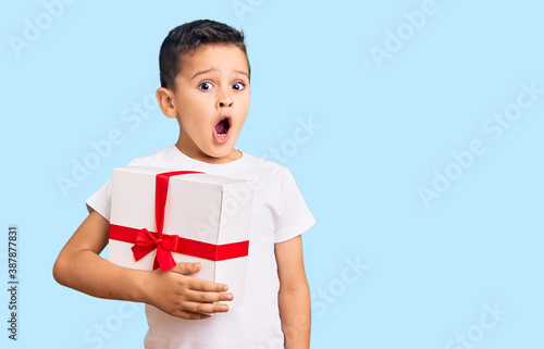 Little cute boy kid holding gift scared and amazed with open mouth for surprise, disbelief face