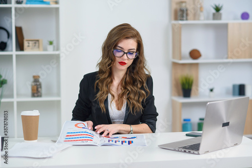 Photo Successful pretty businesswoman at official clothes works with business paperwork and analyses reports at office