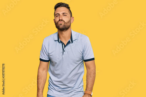 Fotografie, Obraz Handsome man with beard wearing casual clothes looking at the camera blowing a kiss on air being lovely and sexy
