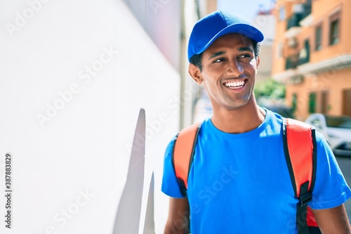 Fotografiet African delivery man wearing courier uniform and backpack outdoors