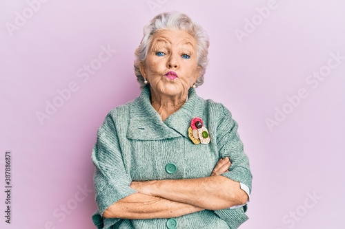 Fototapeta Senior grey-haired woman wearing casual clothes looking at the camera blowing a kiss being lovely and sexy