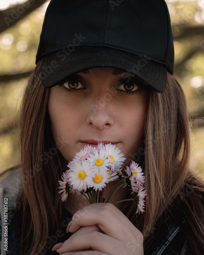 Canvas Print Closeup of an attractive brunette holding a bouqet of small white hand picked flowers on her lips, bright colorful amber eyes looking straight into the camera