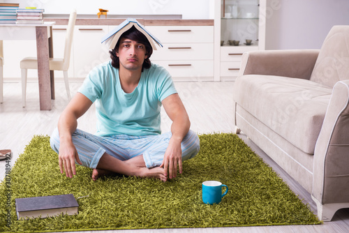 Obraz Young male student unhappy with excessive work at home - fototapety do salonu