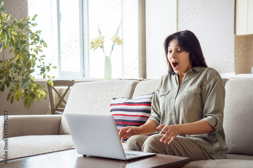 Canvas Print Amazed young indian woman student, customer, lottery winner looking at laptop computer at home reading good news in email feels surprised excited by shopping sale, great exam result, online bid win