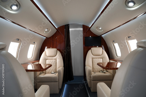 Fototapeta Airplane cabin with comfortable seats and tables