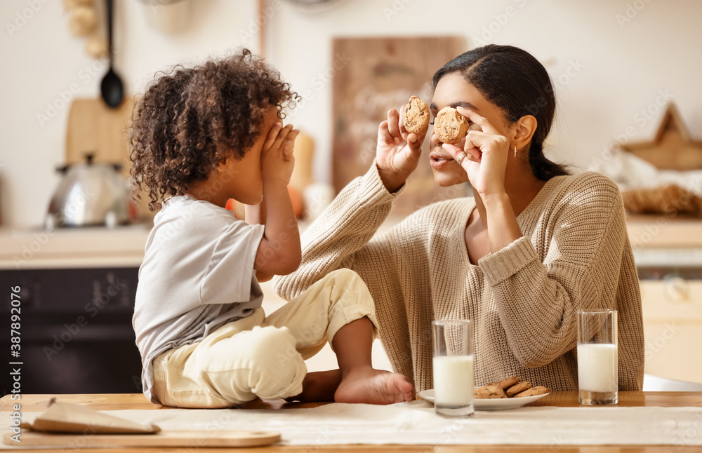 Fototapeta happy african american family: mother and little son eat cookies with milk at home.