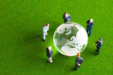 地球儀を見てミーティングをするビジネスマンのミニチュア