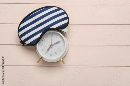 Obraz Alarm clock and sleeping mask on wooden background - fototapety do salonu