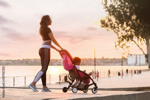 Fototapeta Sporty African-American woman and her cute baby in stroller outdoors