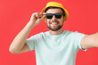 Leinwandbild Motiv Handsome man with stylish sunglasses taking selfie on color background