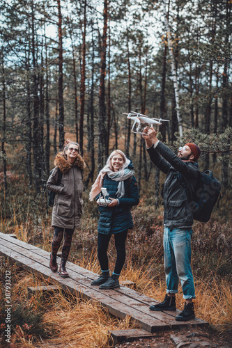 Fotografija Cheerful group of students a guy he holds quadcopter with raised hands and two girls they stay near him in lovely autumn forest