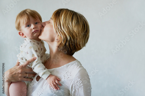 Obraz na plátne Happy emotion Young woman kissing her little On white