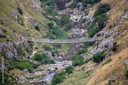 Fotografie, Tablou Simple suspension bridge on the canyon carved by the Gravina River where lies Ma