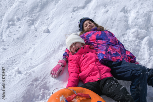 Obraz two delightful laughing kids girls wearing ski suit lying on white snow with rubber tube during winter season travel vacation leisure activity with copy space - fototapety do salonu