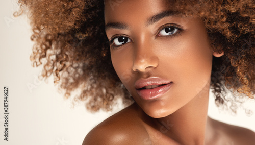 Obraz Beauty portrait of african american girl with clean healthy skin on beige background. Smiling dreamy beautiful black woman.Curly hair in afro style - fototapety do salonu