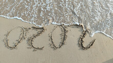 The Inscription On The Sand 2020 With Ocean Wave. The End Of The Terrible Year Caused Coronavirus