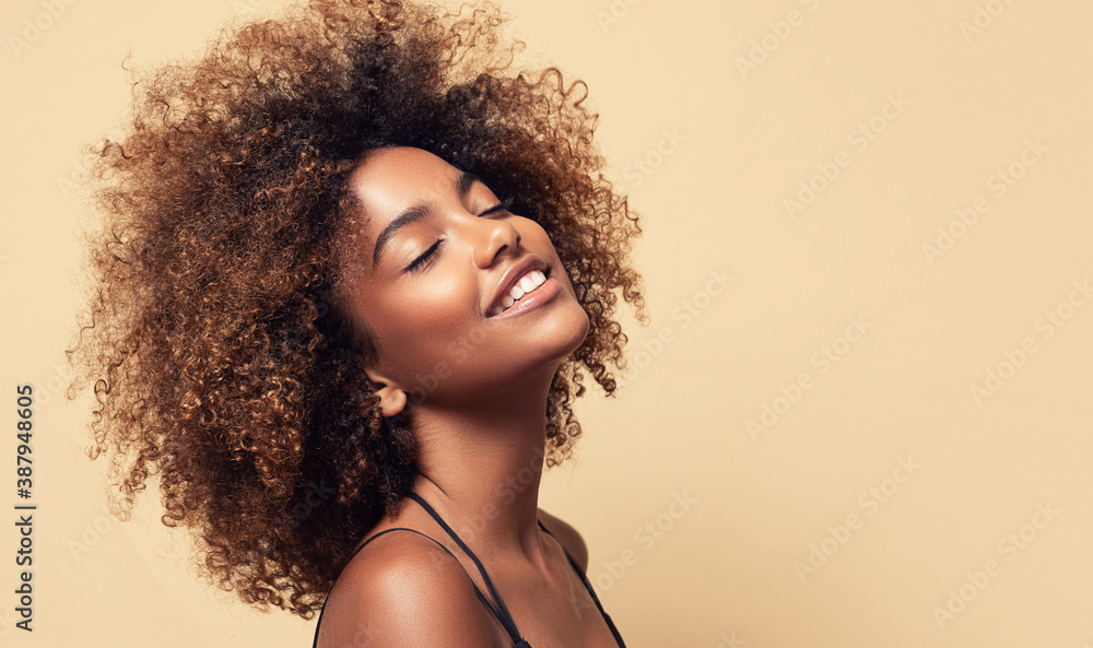 Fototapeta Beauty portrait of african american girl with clean healthy skin on beige background. Smiling dreamy beautiful black woman.Curly  hair in afro style
