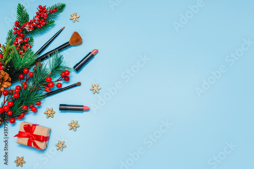 Fototapeta red lipsticks, makeup brushes and a gift lie on a blue background next to spruce branches with red berries