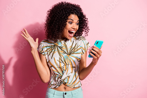 Obraz Photo portrait of shocked screaming girl unexpectedly winning holding phone in hand isolated on pastel pink colored background - fototapety do salonu