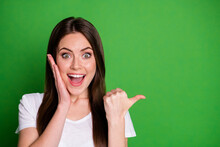 Photo Portrait Of Cheerful Girl Pointing Finger At Blank Space Touching Face With One Hand Isolated On Vivid Green Colored Background