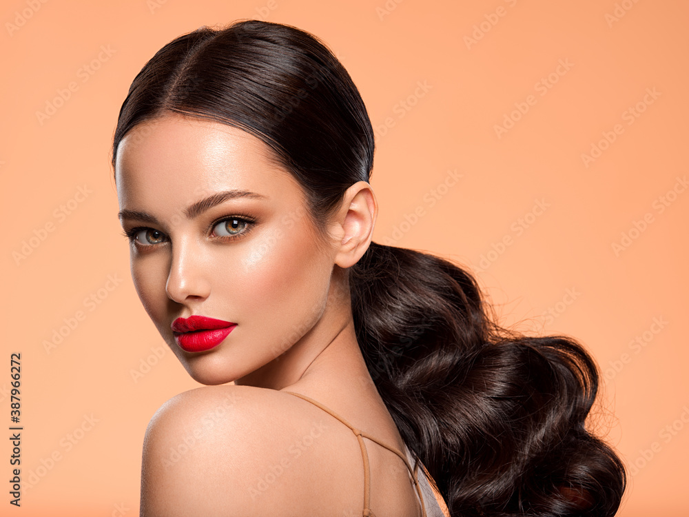 Fototapeta Beautiful white girl with a red lipstick on lips. Stunning brunette girl with long hair tail.  Closeup face of young beautiful woman with a healthy clean skin. Pretty woman with bright makeup