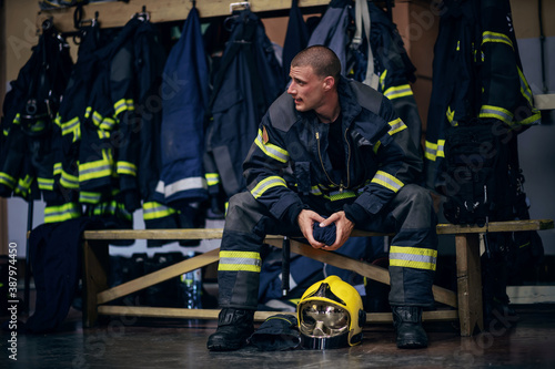 Photo Young attractive fireman in protective uniform sitting in fire station and waiting for other firemen