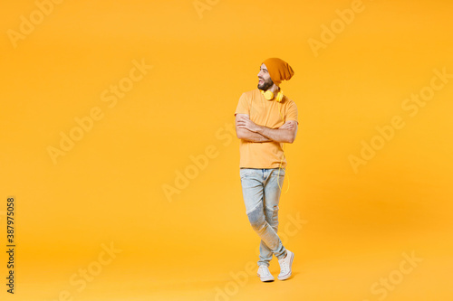 Canvastavla Full length of cheerful laughing young man 20s wearing basic casual t-shirt headphones hat standing holding hands crossed looking aside isolated on bright yellow colour background, studio portrait