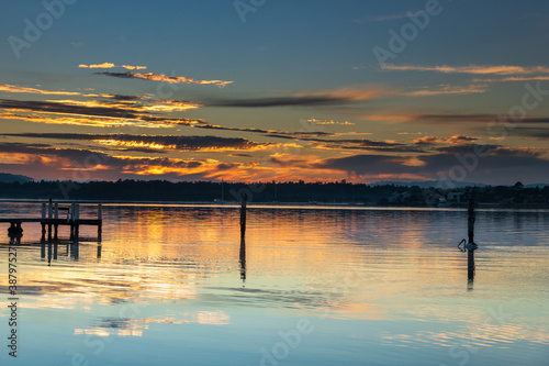 Fototapeta Clouds, reflections and sunrise over the bay obraz