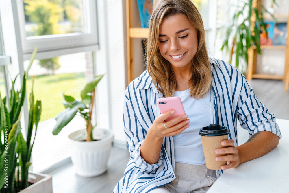 Fototapeta Young caucasian woman holding coffee cup and cellphone in bright room