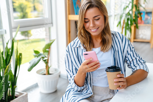 Young caucasian woman holding coffee cup and cellphone in bright room Wallpaper Mural