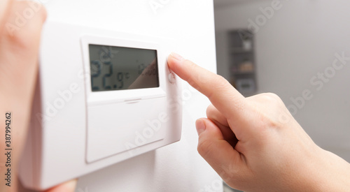 Photo The woman adjusts the thermostat in the house