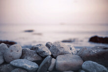 Pebble Stones On The Shore Close Up In The Blurry Sunset Light