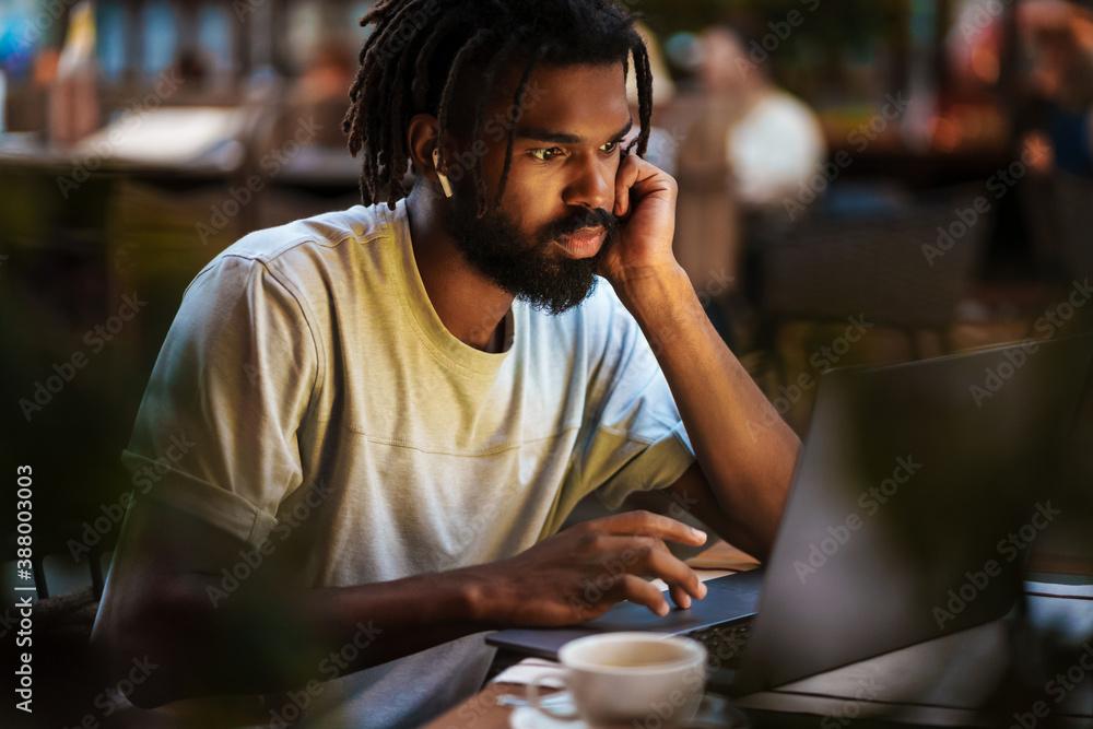 Fototapeta Cheerful african american guy in earphones working with laptop