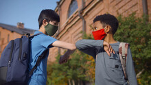 Side View Of Diverse Schoolboys In Protective Mask Doing Elbow Greeting Outdoors