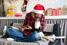 Young Blond Woman In Santa Hat Working On Tablet Sitting On The Couch With Her Dog