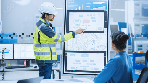 On a Meeting Chief Industrial Engineer Wearing Safety Jacket, and Hardhat Reports to a Group of Specialists, Managers, Uses Interactive Digital Whiteboard to Show New Eco Friendly Engine Technology