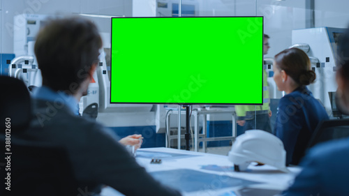 Obraz Modern Factory Office Meeting Room: Diverse Team of Engineers, Managers and Investors Talking at Conference Table, Watching Interactive TV that shows Green Screen Chroma Key Mock-up - fototapety do salonu