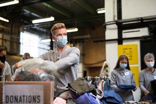 Fotografia Volunteers sorting out donated clothes in community charity donation center, coronavirus concept