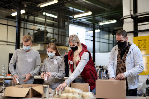 Valokuva Group of volunteers in community charity donation center, food bank and coronavirus concept