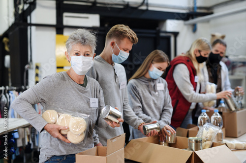 Group of volunteers in community charity donation center, food bank and coronavirus concept. - 388023849
