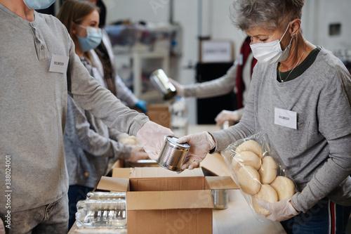 Fototapeta Group of volunteers in community donation center, food bank and coronavirus concept. obraz