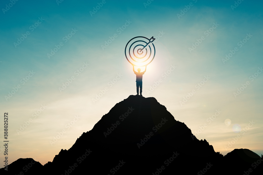 Fototapeta Silhouette of businessman holding target board on the top of mountain with over blue sky and sunlight. It is symbol of leadership successful achievement with goal and objective target.