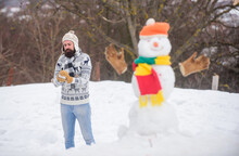 Snowman And Cheerful Bearded Hipster Knitted Hat And Warm Gloves Play With Snow Outdoors. Have Fun Winter Day. Let It Snow. Christmas Holidays. Active Lifestyle. Snow Games. Leisure On Fresh Air