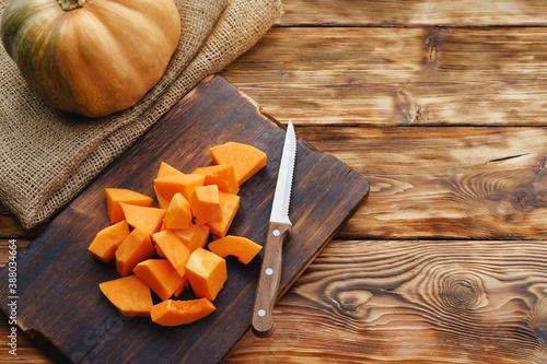 Fotografia Cut pieces of raw pumpkin on wooden board on table